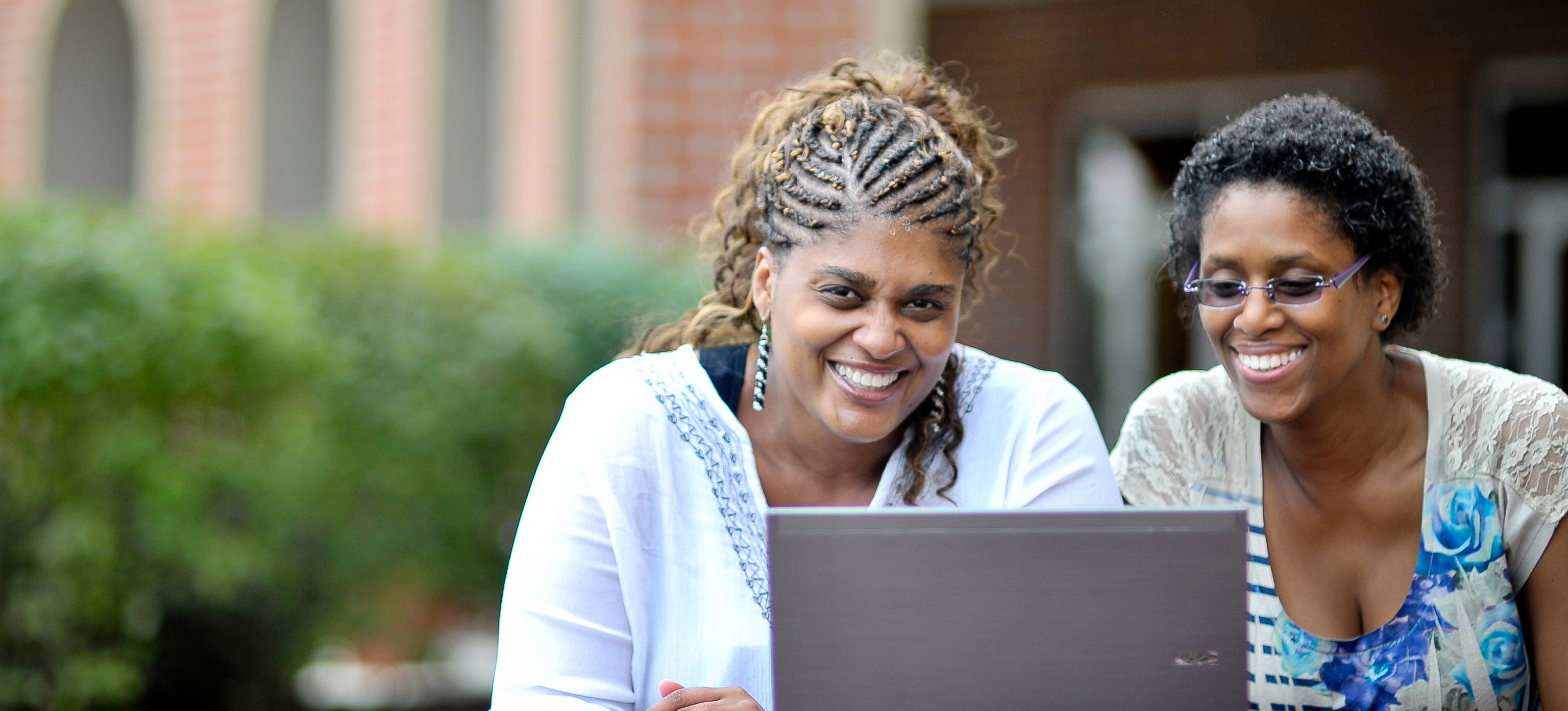 2 smiling women on laptop outside GSLC campus