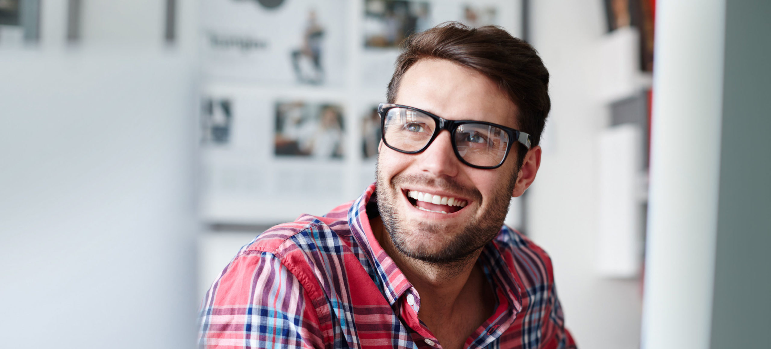 Happy grinning man in glasses and plaid shirt
