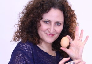 Woman in blue shirt holding an egg up to show the camera